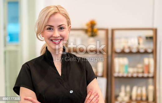 Portrait of a happy business owner working at a spa selling products and looking at the camera smiling - beauty concepts