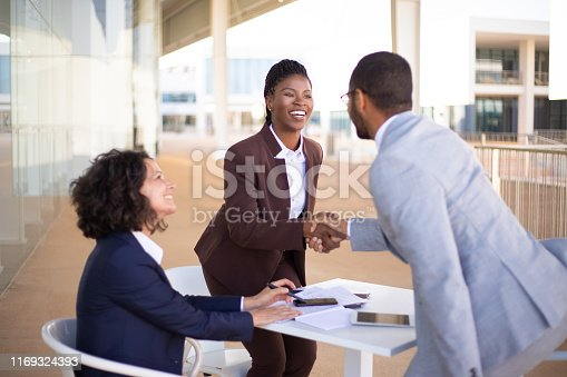 Happy business partners meeting in outdoor cafe and greeting each other. Business man and women standing and sitting at table outdoors, shaking hands, talking and smiling. Partners meeting concept