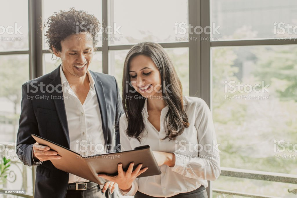 Happy business partners reading contract terms stock photo