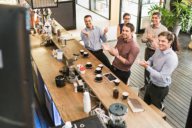 Happy business people applauding at coffee counter stock photo