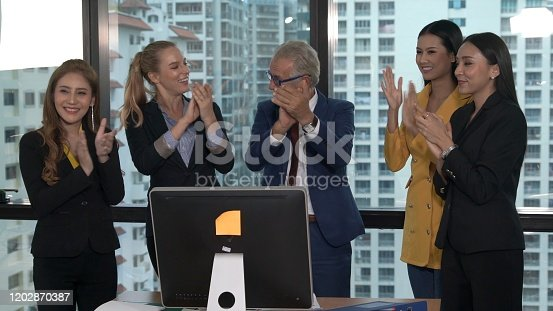 938516440 istock photo Happy business people celebrate victory of success 1202870387