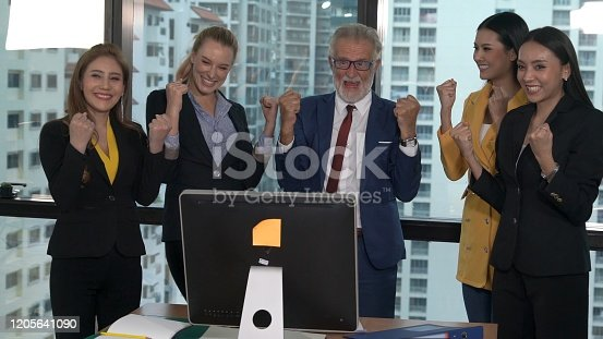 938516440 istock photo Happy business people celebrate victory of success 1205641090