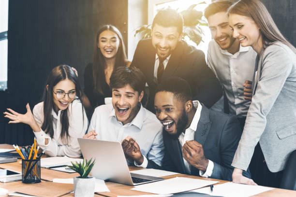 幸せなビジネスの人々 のラップトップを見て成功を祝う - ドキドキ ストックフォトと画像
