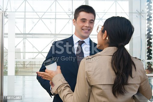 Happy business people gesturing and discussing ideas outdoors. Business man talking with woman who is standing back to camera with building glass wall in background. Colleagues or partners concept.