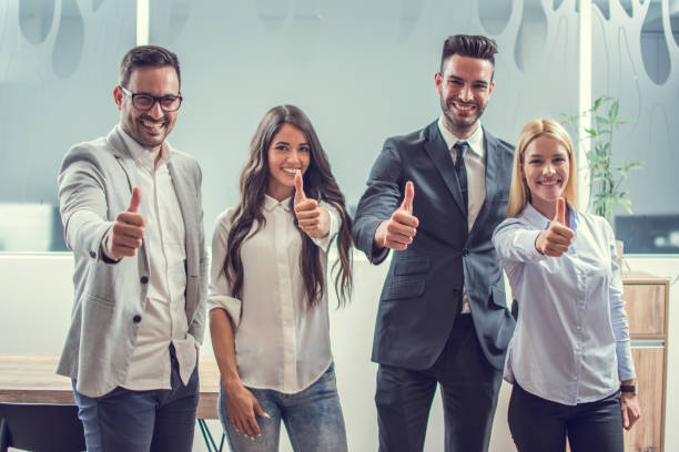 Happy business people showing thumbs up while standing in the office. stock photo