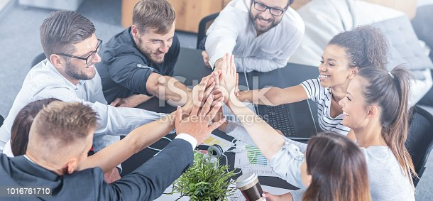istock Happy business people team giving high five in office. 1016761710