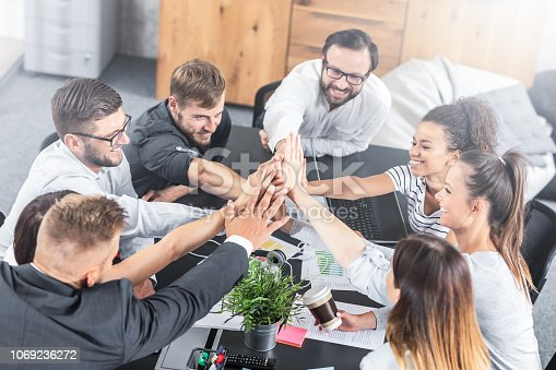 istock Happy business people team giving high five in office. 1069236272