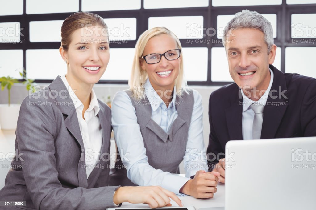 Happy business people with laptop at desk royalty-free stock photo