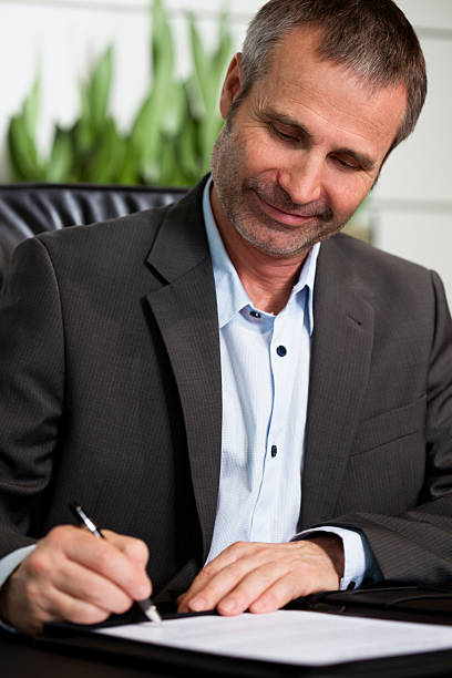 Happy business person signing a contract. stock photo