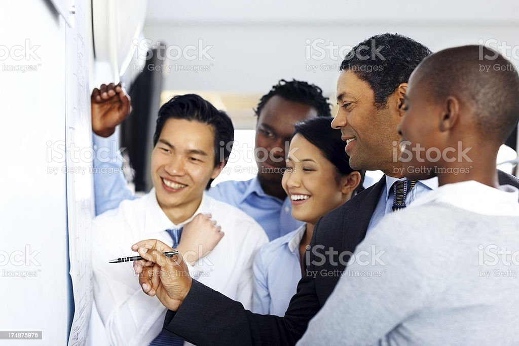Happy business professional looking at building plan royalty-free stock photo