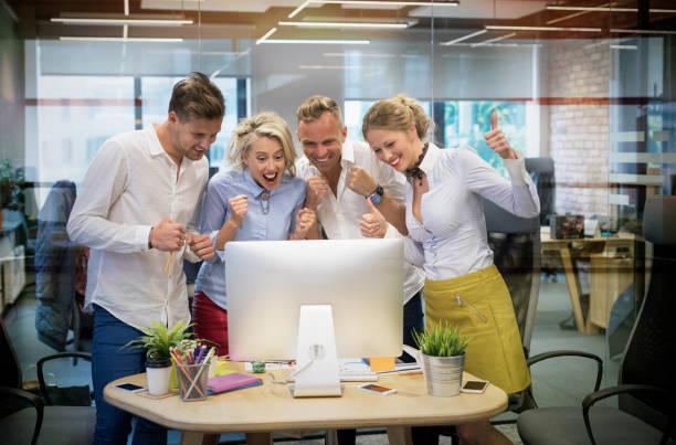 happy business team feiert erfolg bei der arbeit - gute webseiten stock-fotos und bilder