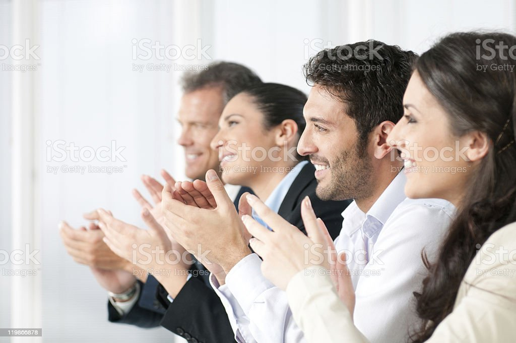 Happy business team clapping hands stock photo