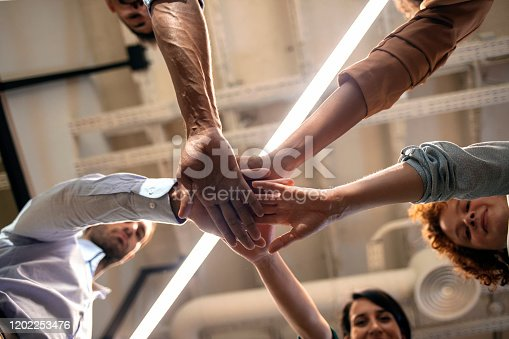 1174511028 istock photo Happy business team giving high five in office 1202253476