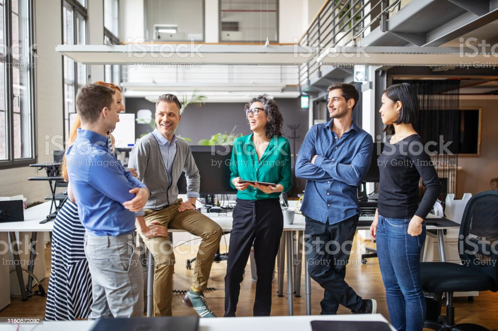 Happy business team having a standing meeting in office - Royalty-free Adult Stock Photo