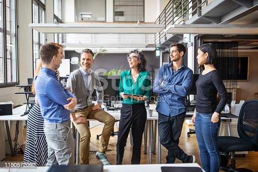 Group of multi-ethnic business people having a meeting in office. Businessmen and businesswoman having a standing meeting in modern office.