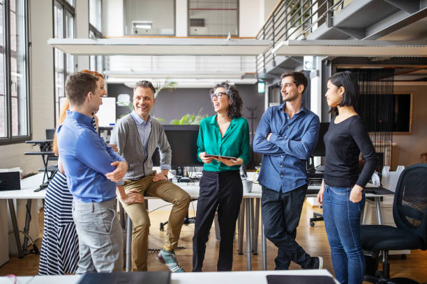 Happy business team having a standing meeting in office stock photo