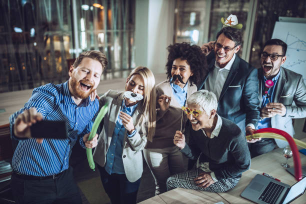happy business team having fun while taking a selfie at office party. - office party stock pictures, royalty-free photos & images