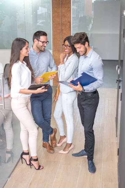 Happy business team having meeting in office hallway and discussing documents. stock photo