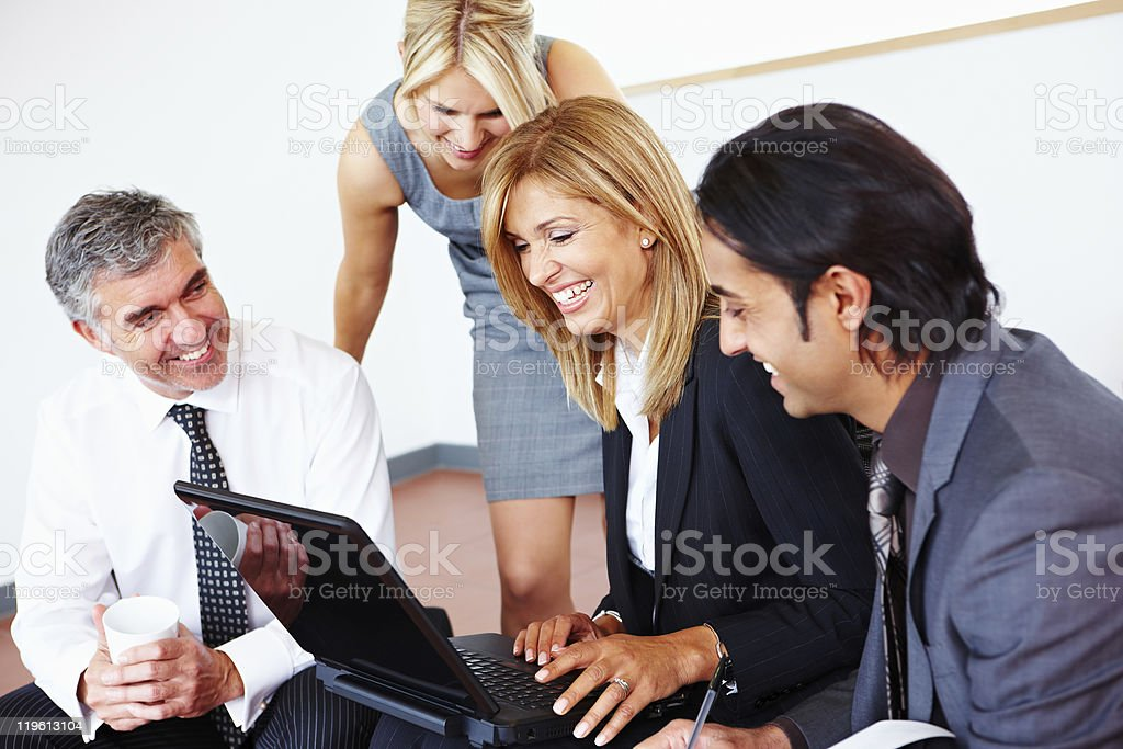 happy business team looking at laptop in meeting royalty-free stock photo