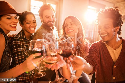 Group of cheerful colleagues toasting with wine to a good business deal.