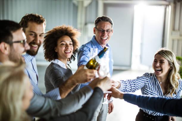happy business team toasting with champagne at office party. - офисные вечеринки стоковые фото и изображения