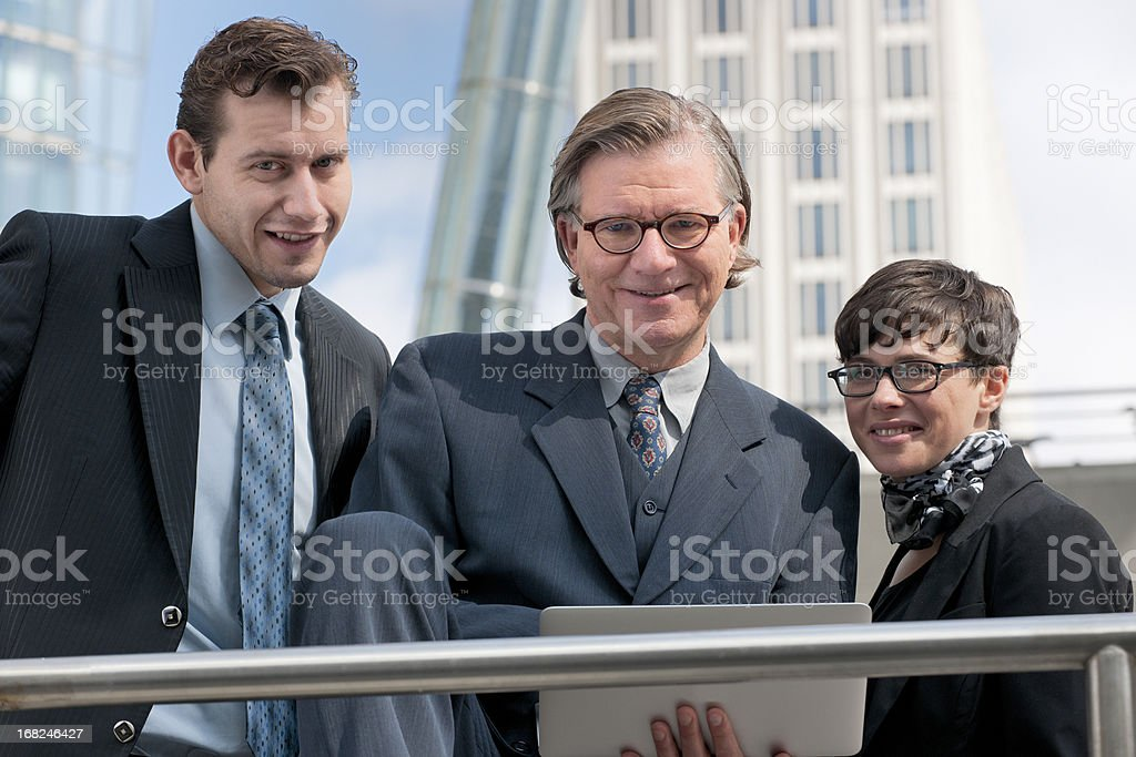 happy business team using laptop in front of office building stock photo