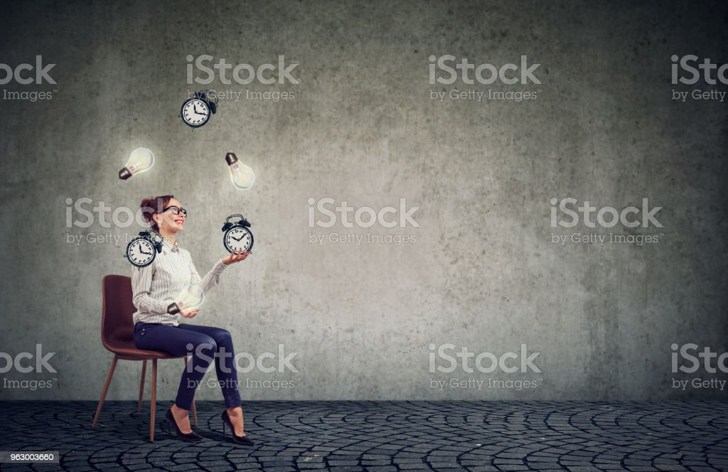 Happy business woman juggling dollar signs and time alarm clock stock photo