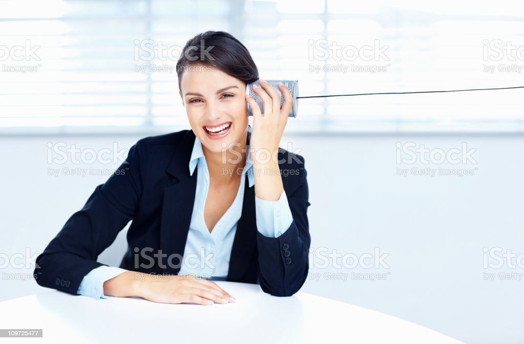 Happy business woman listening through a tin can phone royalty-free stock photo
