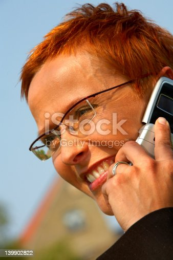 1150572074istockphoto Happy business woman making a phone call. 139902822