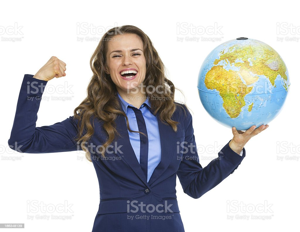 Happy business woman showing earth globe and biceps stock photo