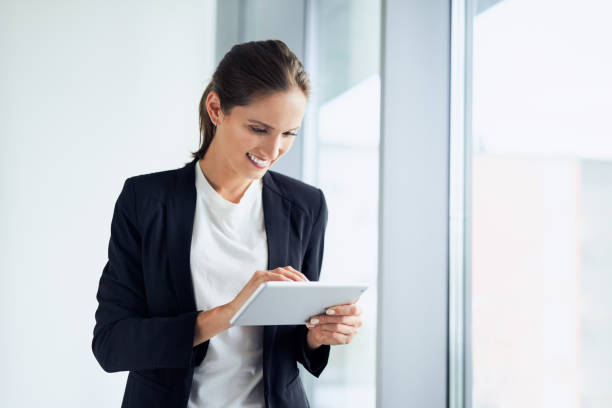 Happy business woman using tablet at corporate office stock photo