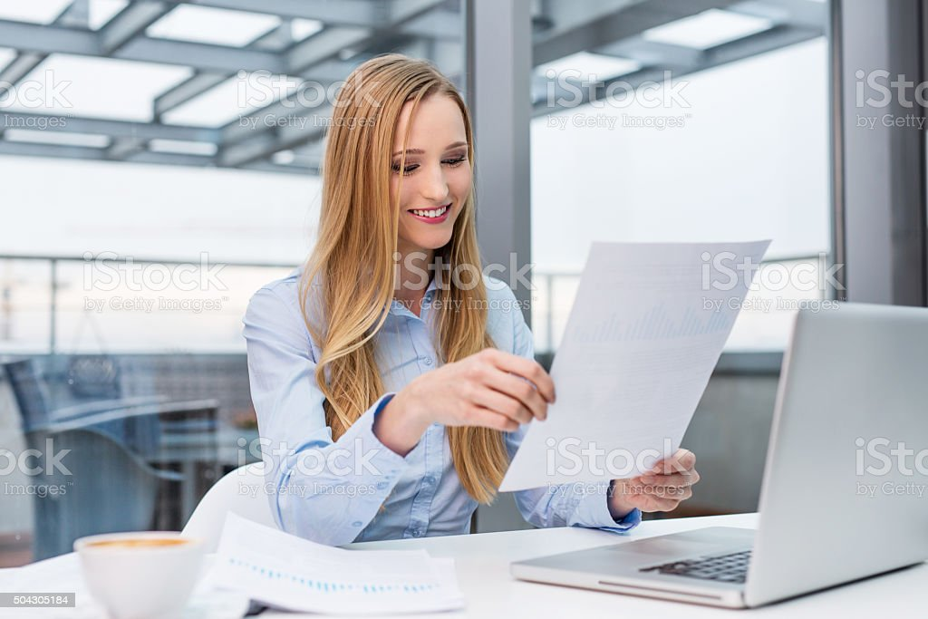 Happy business woman working at desk stock photo