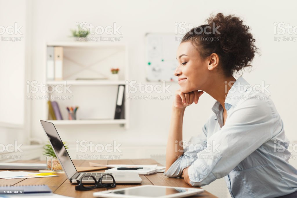 Happy business woman working on laptop at office stock photo