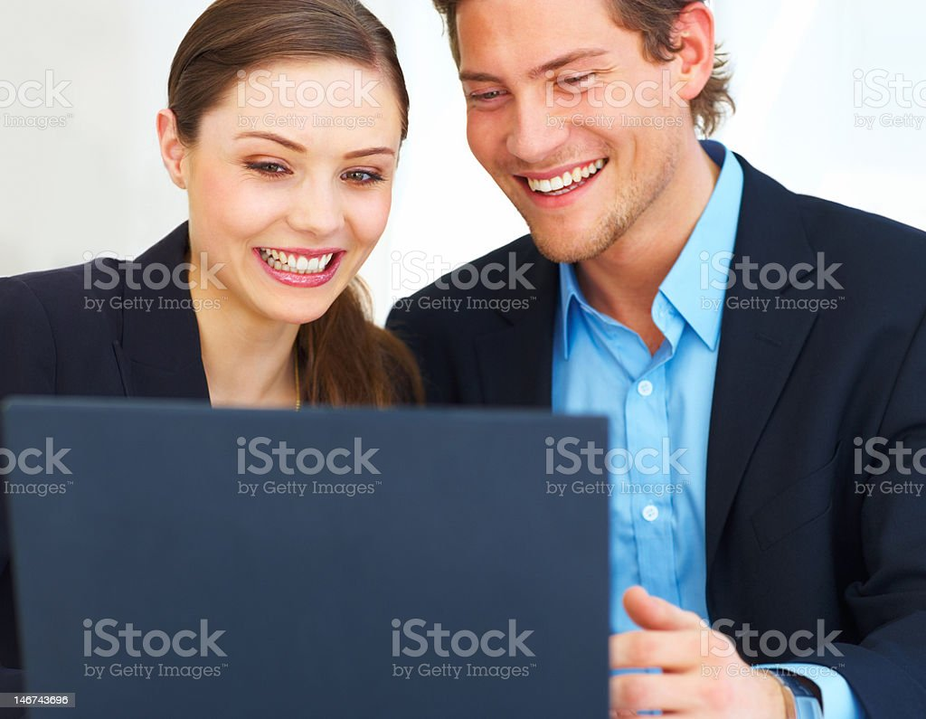 Happy businessman and businesswoman looking at laptop royalty-free stock photo