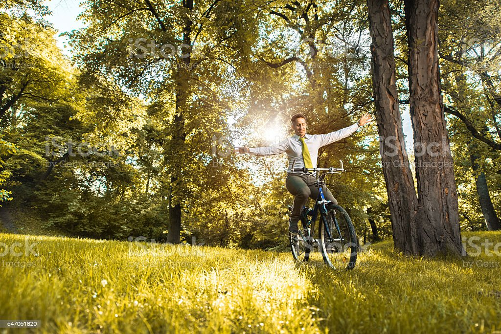 Happy businessman balancing while cycling in the park. stock photo
