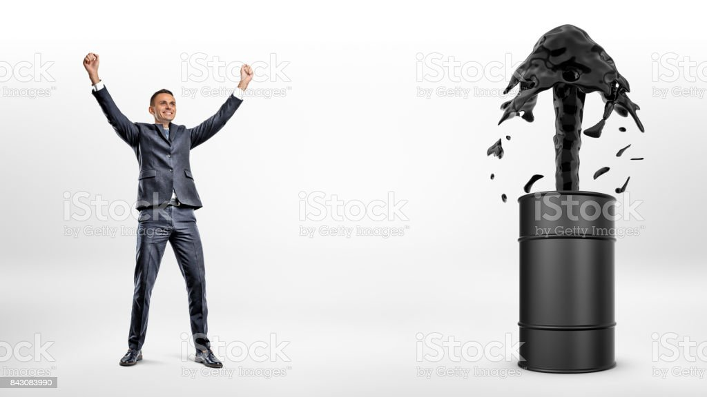 A happy businessman beside a black barrel with a strong current of oil flowing out of it stock photo