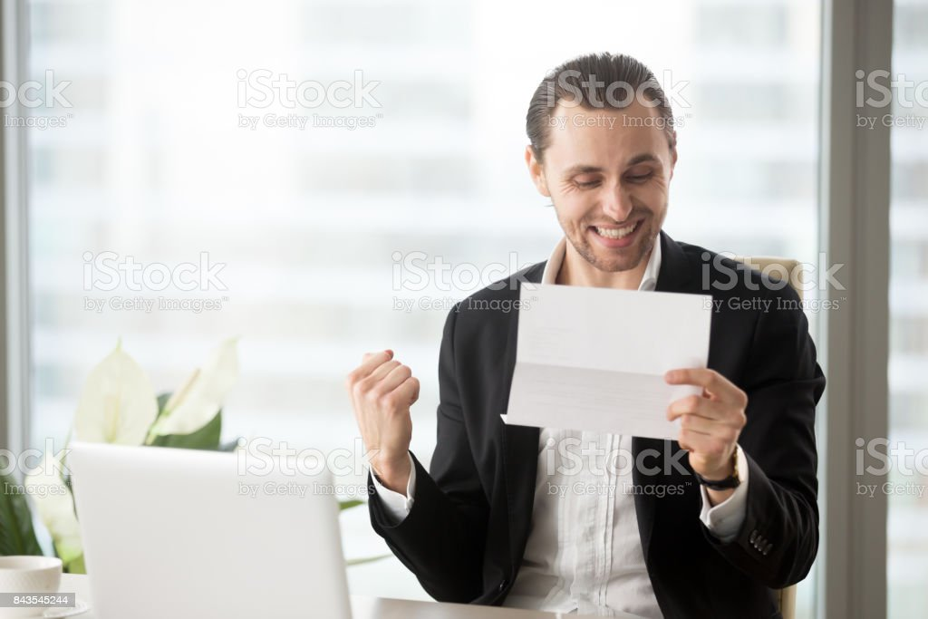 Happy businessman celebrates receiving good business news in letter. stock photo