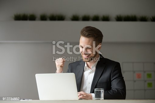 istock Happy businessman celebrating business success online win looking at laptop 912234852
