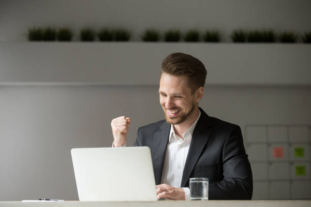 happy businessman celebrating business success online win looking at laptop - excited emoji stock photos and pictures