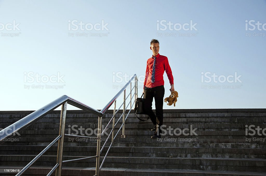 Happy businessman come down the stairs stock photo