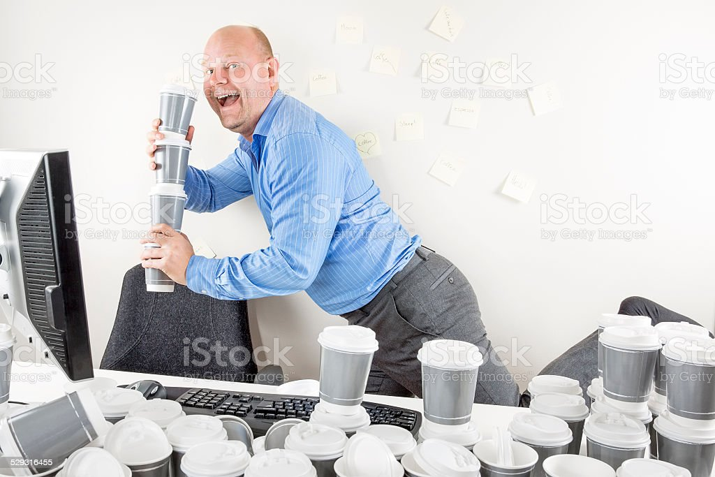 Happy businessman drinks too much coffee stock photo