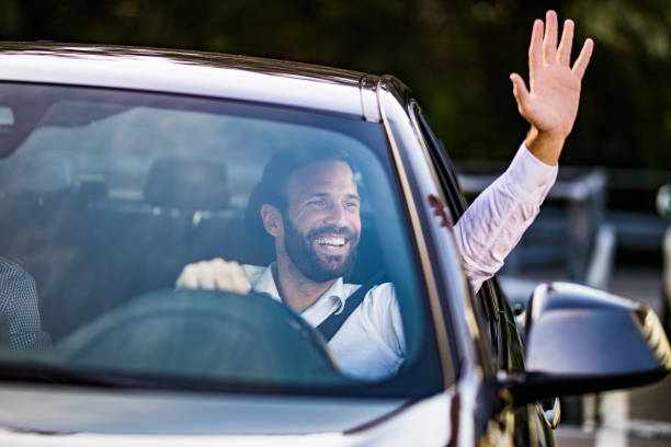 heureux homme d'affaires, conduire une voiture et en agitant à quelqu'un. - homme faire coucou voiture photos et images de collection
