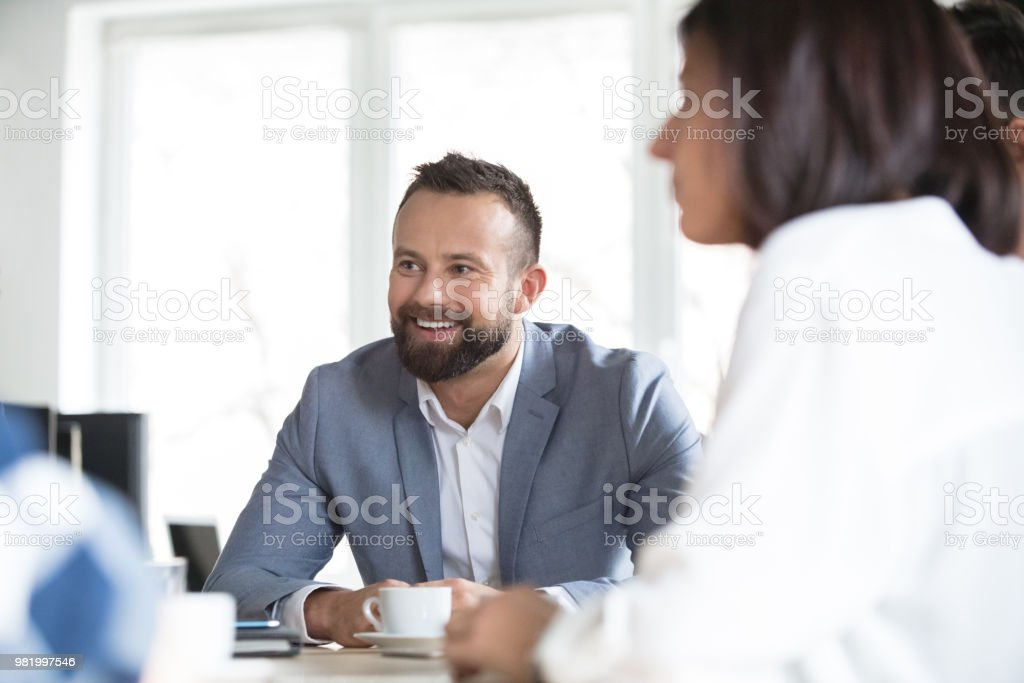 Happy businessman during meeting Mature businessman smiling during a meeting with colleagues. Conference meeting of corporate professionals. Adult Stock Photo