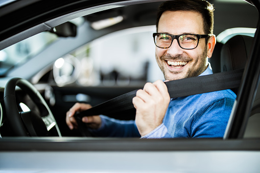 Young happy man fastening his seatbelt before a trip by car and looking at camera.