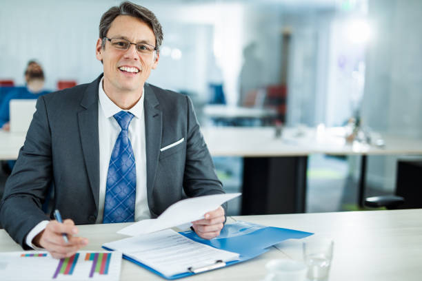 happy businessman going through financial reports in the office. - bankers stock photos and pictures