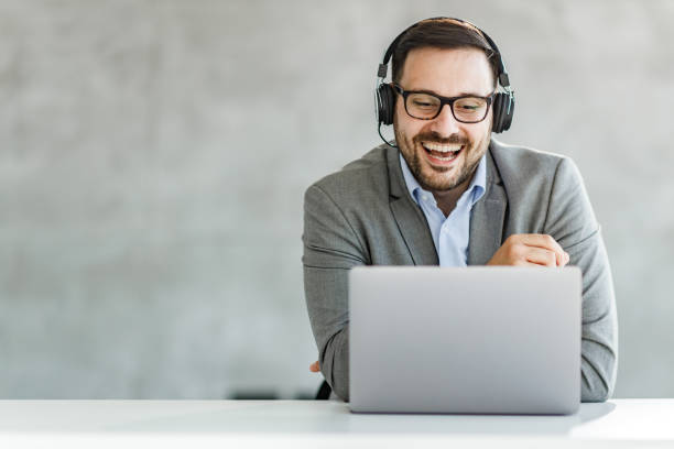 Happy businessman having a video call over laptop in the office. stock photo