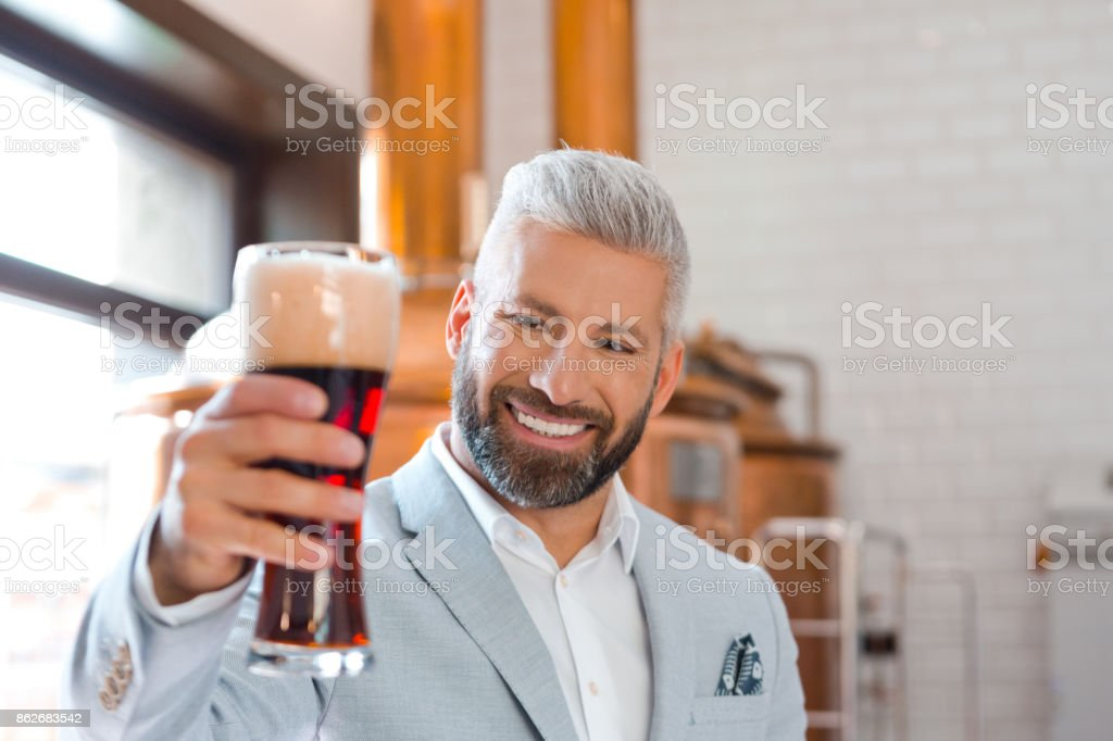 Happy businessman holding a beer glass in his pub Happy microbrewery owner standing in front to copper vat and holding beer glass. Adult Stock Photo