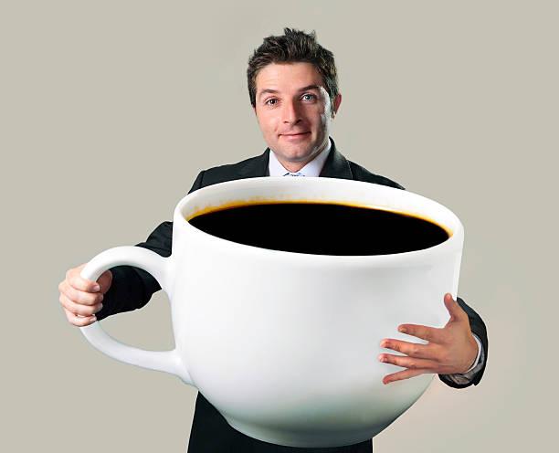 Glücklich Geschäftsmann holding lustiger riesige Große Tasse schwarzen Kaffee- – Foto