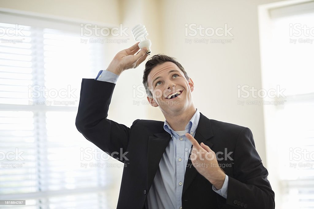 Happy Businessman Holding Light Bulb Over Head royalty-free stock photo