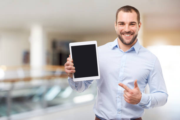 Happy businessman in blue shirt shows touch screen stock photo